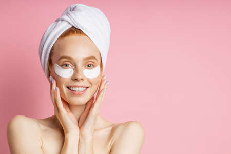 Headshot of sensual beautiful woman applying patches to reduce under eye puffiness and dark circles, touching gently face with both palms, posing naked isolated on pink background. Beauty concept.