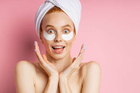 Closeup of surprised cheerful redhead young woman applying moisturizing hyaluronic patches, biting lips, looking to side with happy expression posing over pink background with copy space. Banque d'images