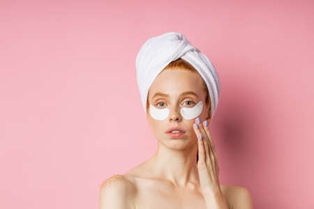 Good looking redhead freckled european woman with hydrogel patches under eyes for reduce eye bags, holding cosmetic sponge, wearing towel on head standing against pink wall. Care, wellness concept. Banque d'images
