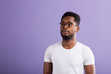 Portrait of intelligent calm young bearded black man in eyewear, dressed in casual clothes looking with puzzlement aside standing against purple studio wall with copy space for your advertising.