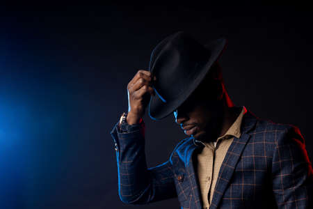 Side view of cool dark skinned man in stylish suit, touching his black hat, looking down. Closeup portrait of fashionable african american male model posing on dark background with backlight.