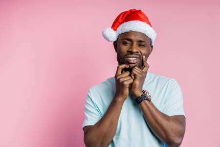 Thoughtful dark skinned man with stubble in Santa hat keeping hands on face, trying to make decision, or remember something important, thinking isolated over pink background with copy space.