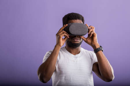 Closeup portrait of afro american man wearing VR goggles, working over virtual project, enjoying new reality, playing video game, posing isolated against violet wall. Technology, innovation gadgets.
