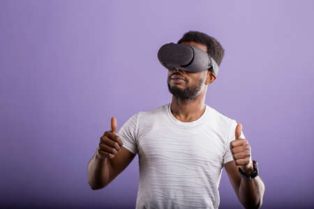 Dark skinned young man experiencing virtual reality, showing thumb up, playing video games using rift headset. 3d technology, innovation, entertainment, cyberspace concept. Banque d'images