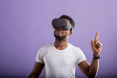 Cute african american man in VR glasses, playing video games with virtual reality headset, interacting with invisible screen on lilac background with copy space. 3D technology, VR concept.