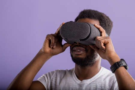 Young dark skinned man dressed in casual outfit wearing mobile virtual reality headset for playing 3D game isolated on purple background. VR technology, innovation and gaming concept. Banque d'images