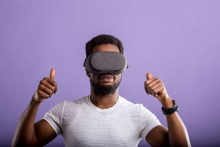 Dark skinned young man experiencing virtual reality, showing thumb up, playing video games using oculus rift headset. 3d technology, innovation, entertainment, cyberspace concept.