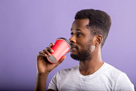 Charming bearded black male dressed casually, enjoying coffee break, drinking hot beverage from red paper cup, looking away standing against lilac background. Leisure concept.