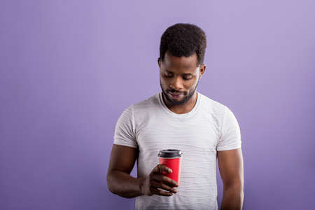 Young african man with short curly hair, enjoying free time, wearing casual white tshirt, holding takeaway coffee, isolated over purple background, drinking tasty beverage. People and leisure. Banque d'images