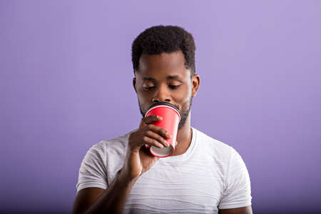 Attractive young Afro American man enjoying fresh takeaway coffee in red paper cup standing against violet background. People and lifestyle concept. Close up. Time for coffee break. Banque d'images