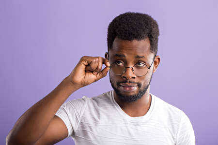 Headshot portrait of concentrated amazed attractive young black man touching glasses trying to read text, recognize someone, astonished with low prices isolated on violet background.
