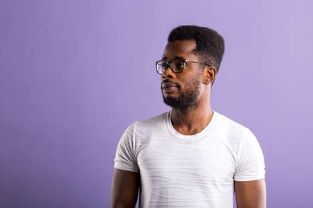 Thoughtful relaxed and handsome african man with beard wearing glasses and casual outfit looking left with serious expression, saw something interesting. Copy space for your advertising. Banque d'images