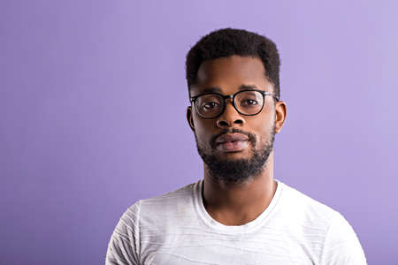 Portrait of handsome young African American male in glasses dressed in white t shirt looking at camera with serious and confident expression. People and lifestyle concept. Copy space. Banque d'images