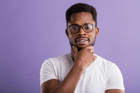 Cheerful african guy in glasses dressed in white t shirt smiling having good mood touching chin while posing in studio over violet background. Facial expressions concept. Copy space.