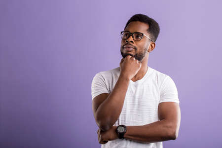 Dark skinned man with short curly hair in casual outfit holding chin with hand, looking aside with interested dreaming expression, thinking about something on violet background with copy space. Banque d'images