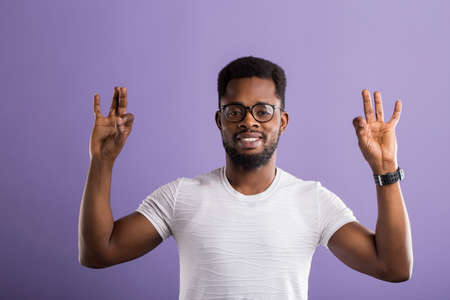Charming happy young African American man in eyewear, white tshirt gesturing, showing Ok sign with both hands and smiling on violet background. Body language, positive facial expressions, emotions. Banque d'images