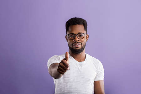 Portrait of satisfied good looking african american man with beard in glasses, casual white tshirt showing thumb up smiling with happy expression on lilac background. Close up, copy space.