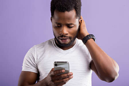 Photo of amazed puzzled black man holding modern cell phone, receiving unexpected message, reading shocking news, isolated over lilac background. Reaction, technology, facial expressions concept.