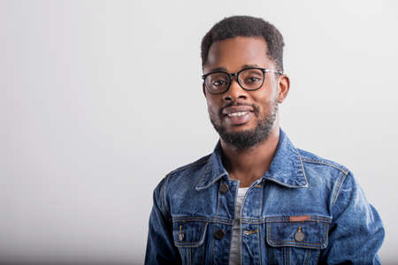 Horizontal close up portrait of joyful happy african guy in spectacles denim jacket smiling broadly with laugh teething looking at camera over gray background. Facial expressions and emotions concept. Banque d'images