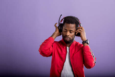 Pleased relaxed bearded stylish dark skinned man listening romantic song in modern black headphones, enjoying with closed eyes on violet background. Positive emotions, enjoyment, music.