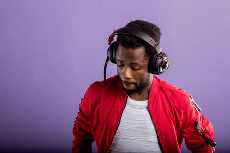 Studio portrait of handsome young black man in headphones, enjoying listening to music and dancing on lilac background. Professional african american DJ in headphones. Close up. Banque d'images