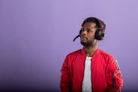 Shot of dark skinned male with bread listening attentively audiobook on headphones, wearing red windbreaker jacket lookig pensively down, has thoughtful expression, gesturing with hands. Copy space.