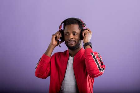 Pleased relaxed bearded stylish dark skinned man listening romantic song in modern black headphones, enjoying on violet background. Positive emotions, enjoyment, music.