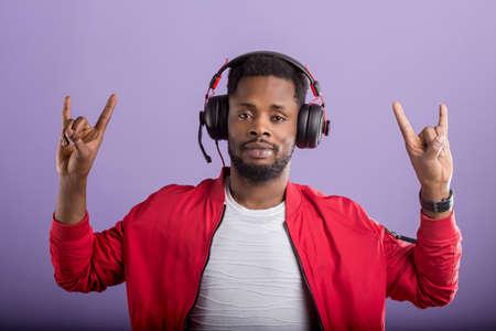 Cool serious african american man dressed in wearing red windbreaker jacket, dancing, listening to music in modern headphones on purple studio background.