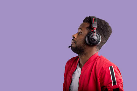 Side portrait of a beautiful afroamerican men in a red sports jacket and headphones on purple background with copy space. Music, DJ concept