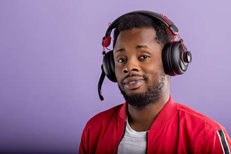 Close-up of beautiful young African American man in headphones on purple background looking at camera