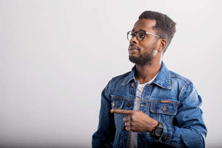 Interested black man pointing with finger at the blank copy space for your text, wearing denim jacket and eyewear, looking to the side. Advertisement and ethnicity concept.