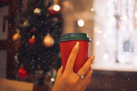 woman holding red paper cup of coffee or hot tea sitting in front of window with garland, christmas lights at cafe. New year, drinks, beverage concept.