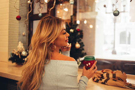 Caucasian european woman sitting at cafe in cozy christmas interior, drinking coffee, looking down with dreamy expression. Sexy blonde waiting boyfriend in cafeteria. New year, winter holidays
