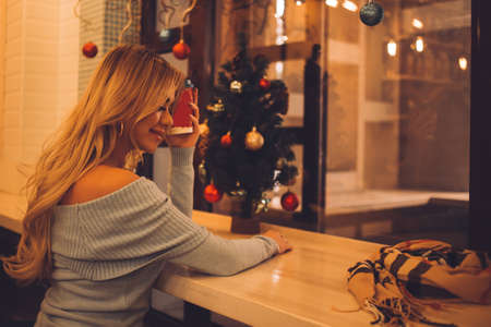 Charming sexy young blonde caucasian woman with long hairsmiling while holding cup of hot drink and enjoying winter evening, looking out window, sitting in cozy cafe decorated for Christmas. Side view Banque d'images