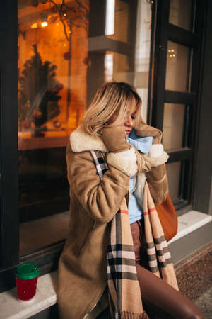 Beautiful blonde girl feeling cold, trying to protect herself from the freeze in city on winter day. Young caucasian woman waiting for friend on the street. Cold weather concept.