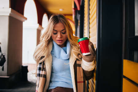 blonde girl walking around the city, smiling, drinking hot coffee, wearing stylish beige coat, mittens and scarf. Lifestyle, people, drinks concept.