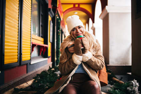 Colorful shot of happy young woman in trendy sheepskin coat, knitted white hat and warm gloves smiling posing with coffee in city street on winter day. Romantic mood. Festive background. Christmas. Banque d'images