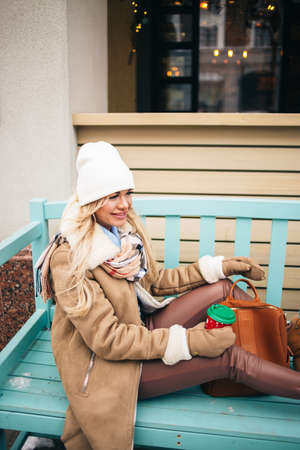 Gorgeous fashionable young blonde woman in beige sheepskin coat, white cap and warm gloves with backpack sitting on blue bench smiling drinking hot cappuccino during snowing. Christmas mood. Banque d'images