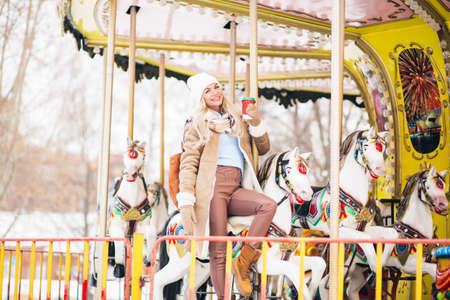 Stunning beautiful young blonde woman in stylish winter sheepskin coat, gloves, knitted hat, with backpack, riding merry-go-round, holding hot coffee in amusement park in city. Winter holidays concept Banque d'images