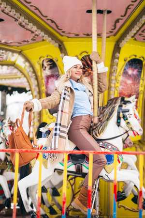 Portrait of attractive lady in trendy clothes with big brown backpack riding merry-go-round holding cup of hot drink, dreaming, spending time in amusement park in weekend. Magic warm new year photo. Banque d'images