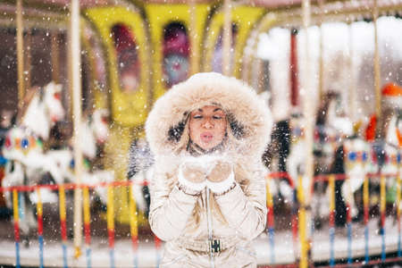 Joyful charming blonde young woman having fun in amusement park in winter. Closeup fashion portrait of happy girl blowing snowflakes from her hands. Enjoying nature. Banque d'images
