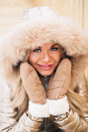 Outdoor portrait of young beautiful happy smiling girl posing on street, sitting on bench, looking at camera, touching cheeks with hands. Lady wearing stylish winter jumpsuit, boots. Female fashion.