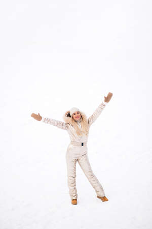 Full-length portrait of blonde european lady wearing stylish golden jumpsuit enjoying free time in winter city, posing with raised hands, smiling to camera. Positive emotions, winter holidays.