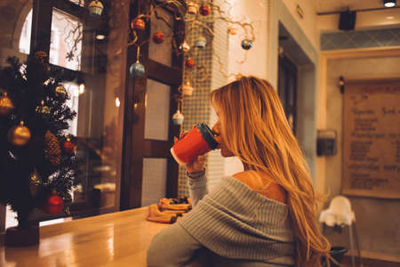 A woman drinks coffee in a cafe on new year's day. Red Cup. blonde lady. New year, holiday