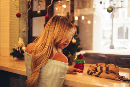 Christmas blonde woman with long hair, back view, drinking coffee near the windowsill. New year, holiday Banque d'images