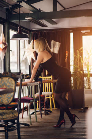 Blonde woman stands sideways, leaning on a table in a restaurant, cafe, wearing a short black dress, red shoes. Sexy girl with a beautiful figure. Full length photo Banque d'images