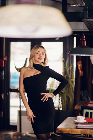 Blonde woman wearing a black short dress looks at the camera in a restaurant, cafe. Sexy, charming young fashion business lady Banque d'images