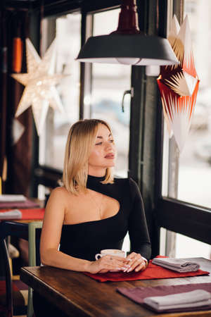 A successful confident business woman sits near the window in a cafe, restaurant and looks at the street. Blonde girl puts on a black dress