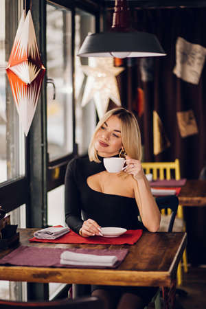 Smiling business woman in a restaurant holding a Cup of tea and looking at the camera, sitting near the window in a black dress Banque d'images