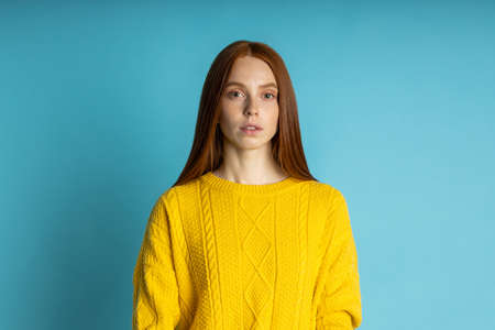 redhead beautiful caucasian young woman with healthy freckled clean skin, in yellow sweater looking at camera with calm and serious expression om blue background. Closeup studio shot